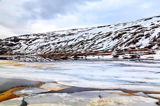 A paisagem de inverno: lago gelado e montanha