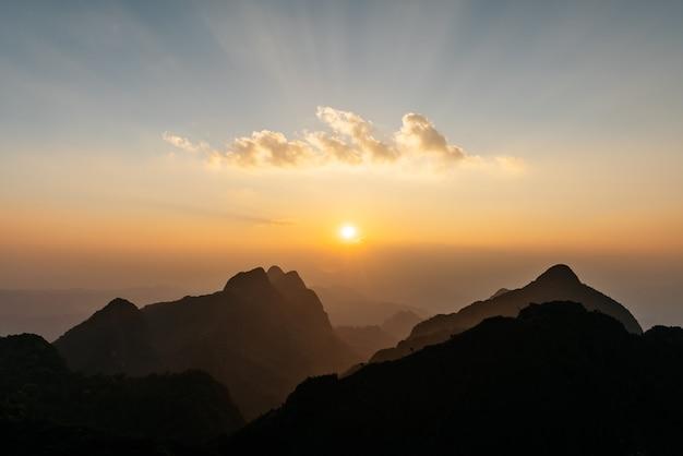 A paisagem de montanhas, nuvem com raio de sol e crepúsculo perto do pôr do sol de doi luang, chiang dao, chiang mai, tailândia.