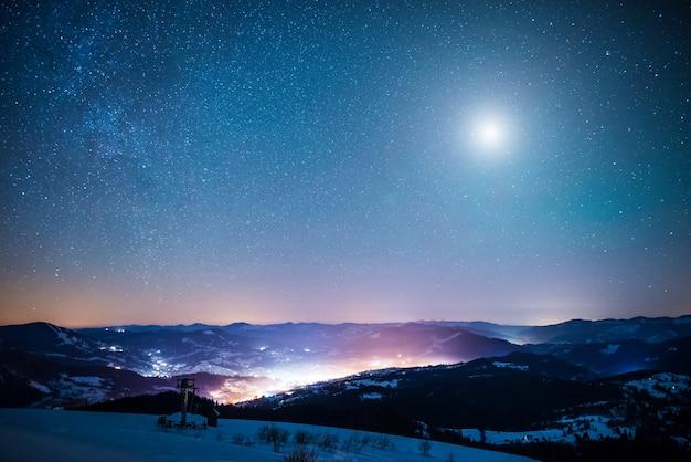 A paisagem hipnotizante de estrelas cadentes no fundo do céu estrelado na vila brilhante está localizada entre altas cadeias de montanhas na noite gelada de inverno. misticismo de conceito de ovnis e fenômenos anormais