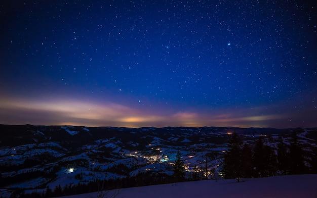 A paisagem mágica da floresta de coníferas crescendo entre as colinas no inverno contra um céu azul estrelado e um pôr do sol carmesim. local para publicidade. lugar para texto
