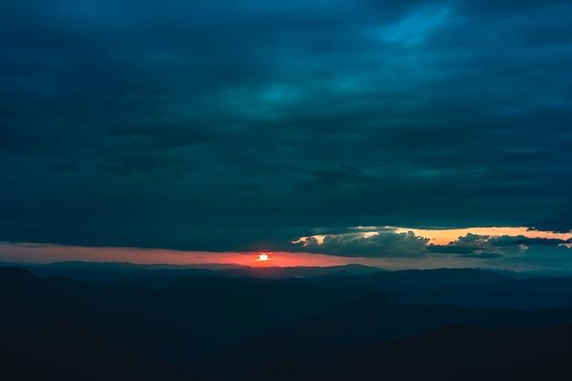 A paisagem montanhosa no fundo do belo pôr do sol