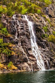 A paisagem pitoresca: cachoeira, pedras e mar
