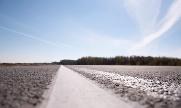 A paisagem pitoresca e o nascer do sol sobre a estrada. estrada de asfalto com marcação. com o borrão.