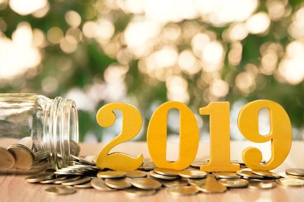 A palavra 2019 pôs sobre moedas e garrafas de vidro com moedas para dentro no fundo verde do bokeh.