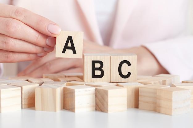 A palavra abc em blocos de brinquedo de madeira com as mãos da mulher, superfície rosa