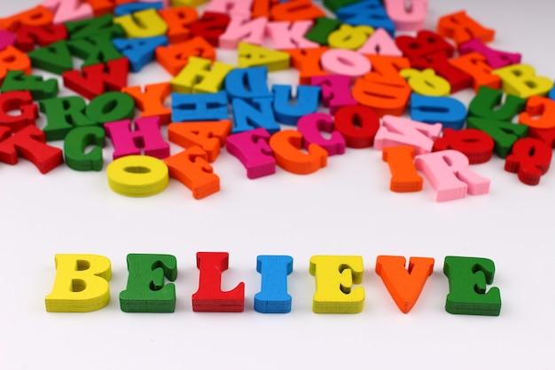 A palavra acreditar com letras coloridas