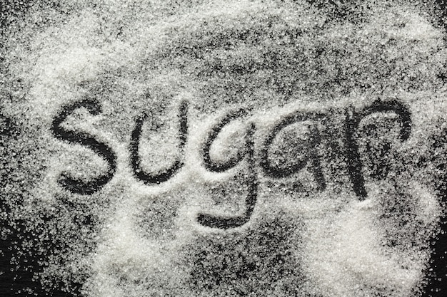 A palavra açúcar escrito em uma pilha de açúcar granulado branco