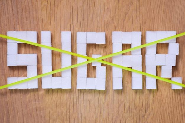 A palavra açúcar, forrada com cubos de açúcar refinado em um fundo de madeira marrom, riscada com duas linhas cruzadas, proibida