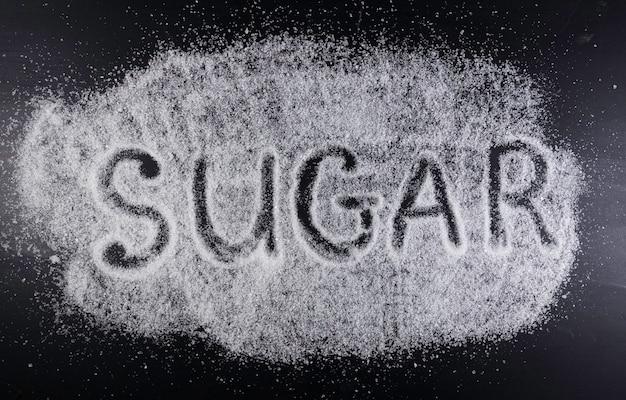 A palavra açúcar no açúcar derramado no fundo preto. danos do açúcar, conceito médico de doença de diabetes.