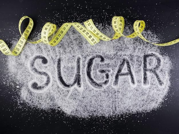 A palavra açúcar no açúcar derramado sobre fundo preto com fita amarela de polegada. danos do açúcar, conceito médico de doença de diabetes.