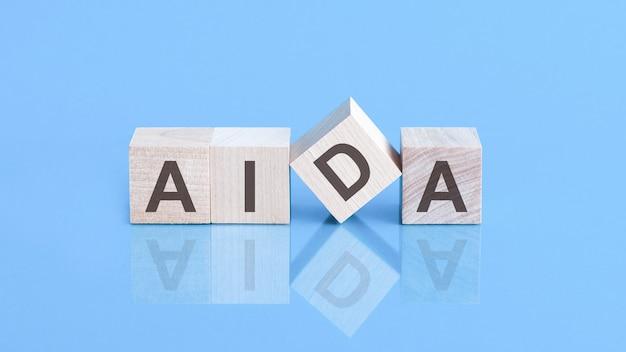 A palavra aida é feita de cubos de madeira sobre a mesa azul, o conceito do negócio. aida - abreviação de attention interest desire action