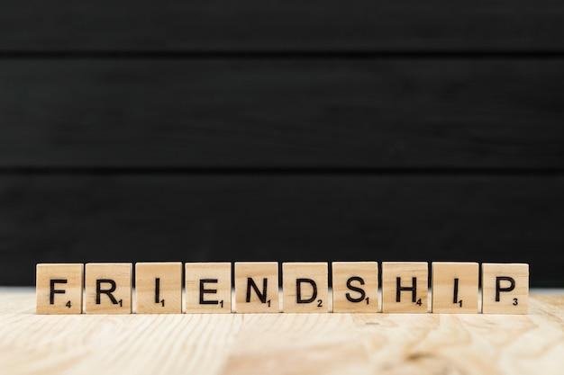 A palavra amizade soletrada com letras de madeira