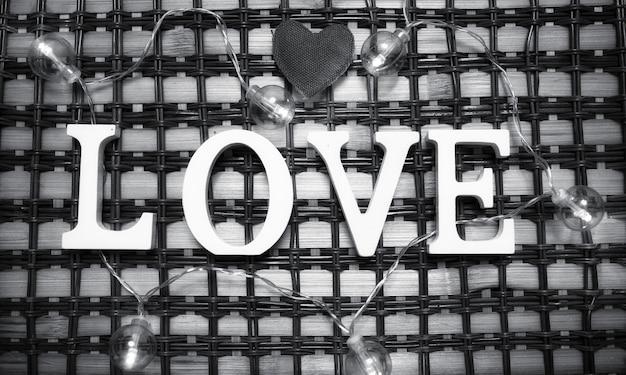 A palavra amor composta de letras de madeira brancas em um fundo de madeira