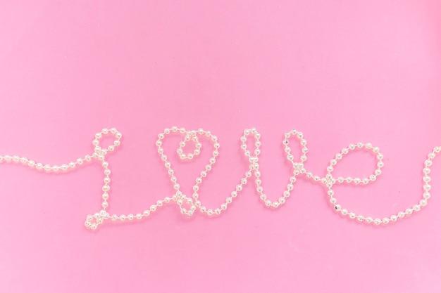 A palavra amor é definida como grânulos em um plano de fundo texturizado rosa. dia dos namorados