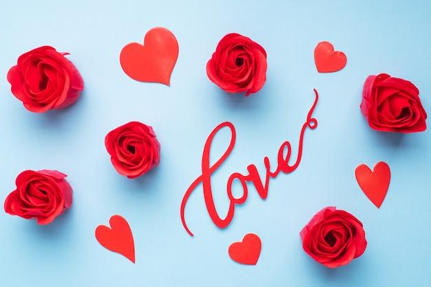 A palavra amor e rosas de corações vermelhos sobre um fundo azul, vista superior. cartão de férias para o dia dos namorados. postura plana.