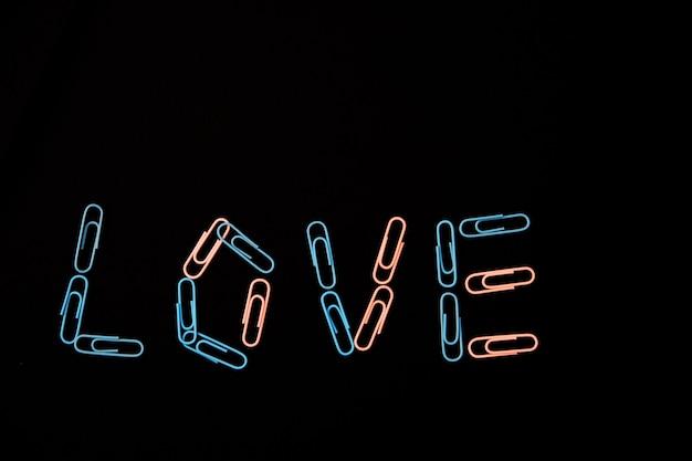 A palavra amor vem de clipes de papel em um fundo preto. os clipes de papel são rosa e azul. o conceito de dia dos namorados.