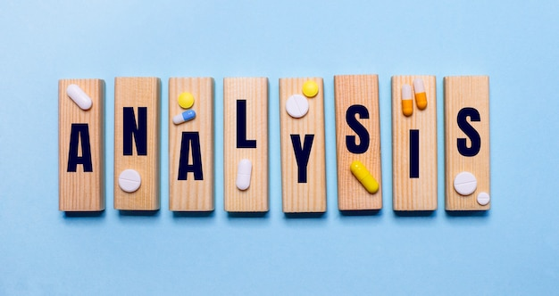 A palavra análise está escrita em blocos de madeira em uma mesa azul clara perto dos comprimidos