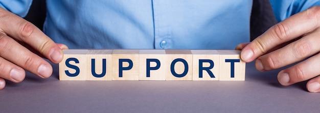 A palavra apoio é composta por cubos de madeira por um homem. conceito de negócios