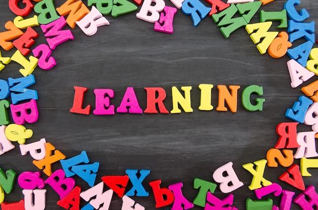 A palavra aprendizagem disposta em letras coloridas em um fundo preto de madeira