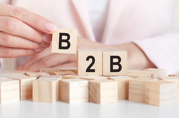 A palavra b2b em blocos de brinquedo de madeira com as mãos da mulher, superfície rosa