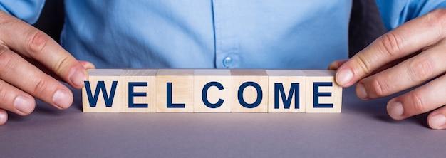 A palavra bem-vindo é composta por cubos de madeira por um homem. conceito de negócios