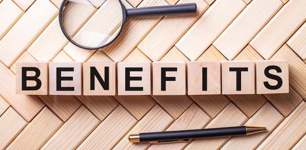A palavra benefícios está escrita em cubos de madeira sobre um fundo de madeira, ao lado de uma alça e de uma lupa.