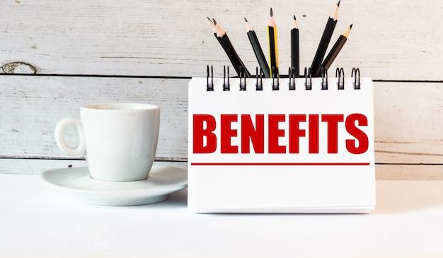 A palavra benefícios está escrita em um bloco de notas branco perto de uma xícara de café branca em uma parede de luz