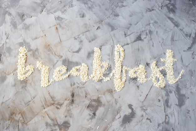 A palavra café da manhã é escrita em um fundo cinza de aveia