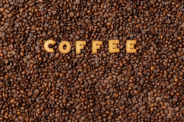 A palavra café feita de letras de biscoito em um fundo escuro de grãos de café