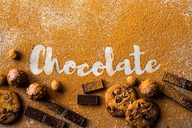 A palavra chocolate impresso no cacau sobre um fundo cinza entre o cacau