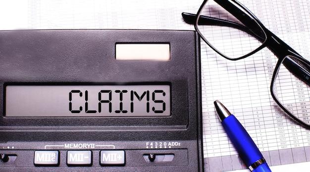A palavra claims é escrita na calculadora perto de óculos de armação preta e uma caneta azul