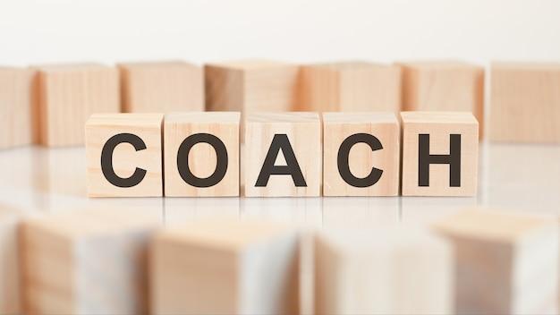 A palavra coach é escrita em uma estrutura de cubos de madeira