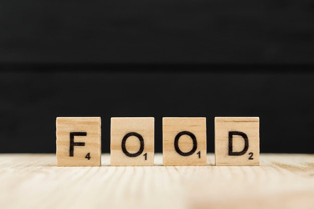 A palavra comida soletrada com letras de madeira