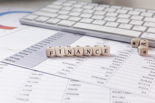 A palavra da finança na imagem de madeira do índice do negócio do cubo.