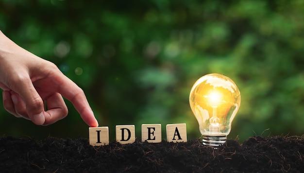 A palavra da ideia em cubos de madeira com lâmpada com conceito de ideia de mão com inovação