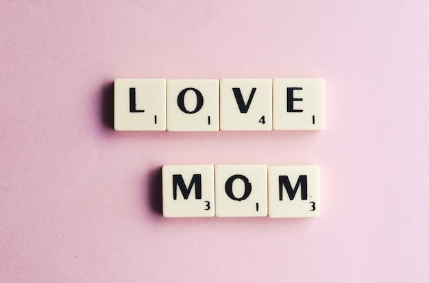 A palavra de amor mamã em cubos de madeira em um fundo rosa