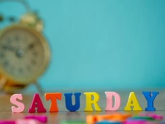 A palavra de madeira colorida sábado na tabela de madeira e no despertador do vintage e no fundo é azul