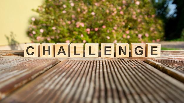A palavra desafio está escrita em cubos de madeira. os blocos são colocados em uma velha placa de madeira iluminada pelo sol. no fundo está um arbusto em flor