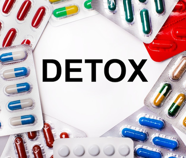 A palavra detox está escrita em branco cercada por embalagens multicoloridas com comprimidos. conceito médico