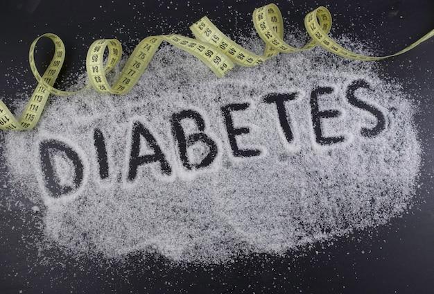 A palavra diabetes no açúcar derramado sobre fundo preto com fita amarela de polegada. danos do açúcar, conceito médico de doença de diabetes.