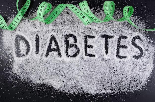 A palavra diabetes no açúcar derramado sobre fundo preto com fita verde de polegada. danos do açúcar, conceito médico de doença de diabetes.