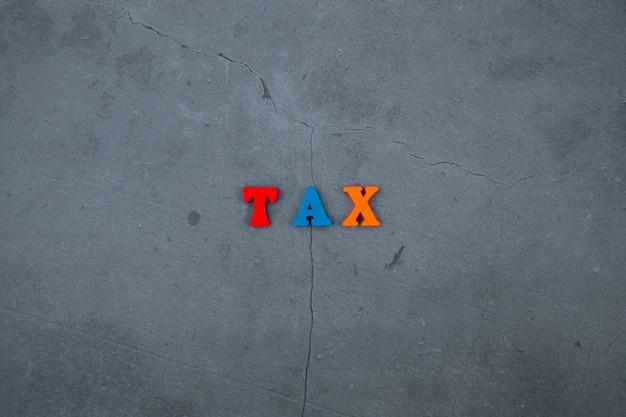 A palavra do imposto multicolorido é feita de letras de madeira sobre um fundo cinza estampado.