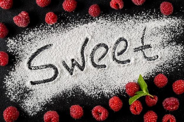 A palavra doce é sobre um fundo escuro ao lado de bagas de framboesa