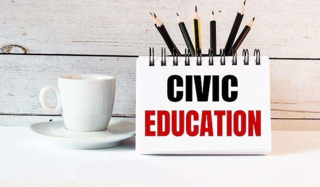 A palavra educação cívica está escrita em um bloco de notas branco perto de uma xícara de café branco sobre uma mesa de luz