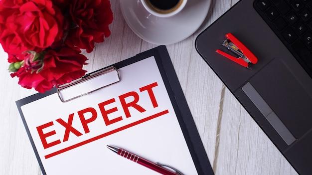 A palavra especialista está escrita em vermelho em um bloco de notas branco perto de um laptop, café, rosas vermelhas e uma caneta