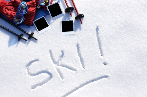 A palavra esqui escrita na neve com bastões de esqui, óculos e chapéus e impressões de fotos em branco