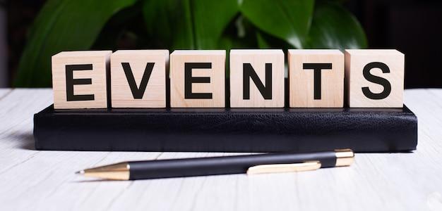 A palavra eventos está escrita nos cubos de madeira do diário perto da alça.