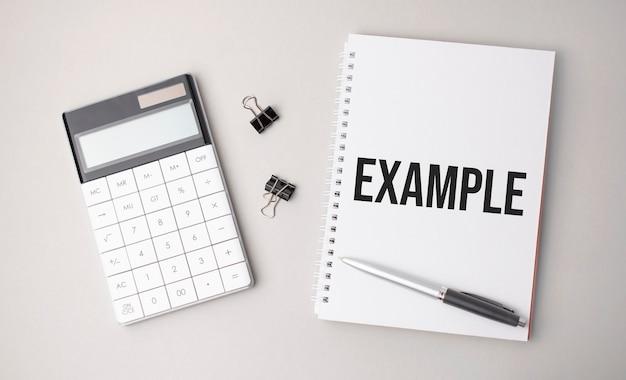 A palavra exemplo é escrita em uma superfície branca ao lado de uma caneta, calculadora e relatórios
