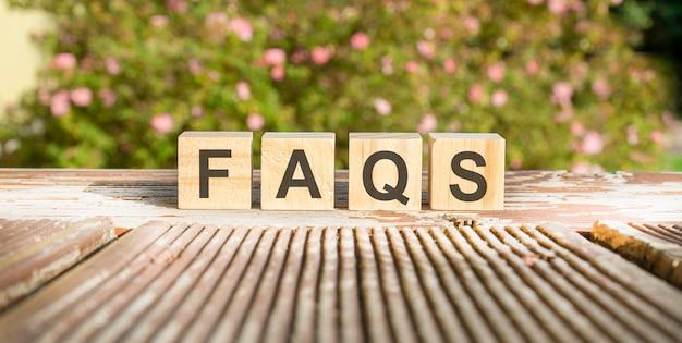 A palavra faqs está escrita em cubos de madeira. os blocos são colocados em uma velha placa de madeira iluminada pelo sol. no fundo está um arbusto em flor