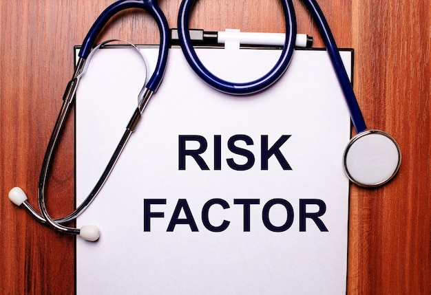 A palavra fator de risco está escrita em papel branco sobre uma mesa de madeira perto de um estetoscópio e óculos de armação preta. conceito médico
